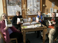 Volunteers and visitors read The Lost World in the CREATE Ecohome in Bristol.