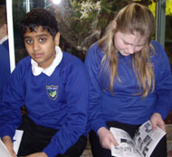 Rushabh and Mary-Lou from New Oak Primary look at their books by the orchid display in Bristol Zoo Gardens' reptile house.