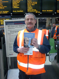 A Scot Rail employee at Waverley Station in Edinburgh on launch day with a copy of Darwin: a graphic biography.