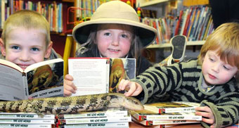 Barry the blue-tongued skink explores some Lost World books at St Austell Library with three new friends.